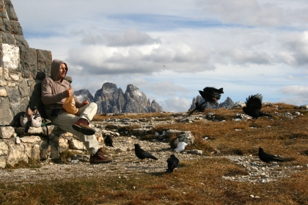 Man feeding crows in front of war monument on a mountainous border between Italy and Austria