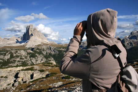 binoculars: Man in a hooded sweat shirt standing in front of mountains in tirol, Italy