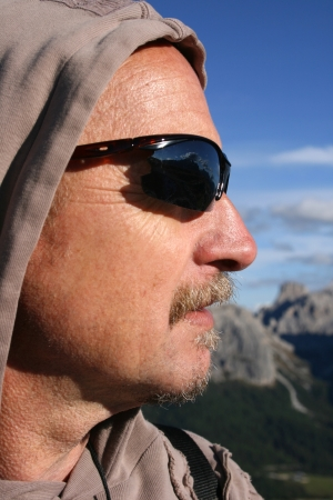 Hooded man in sunglasses standing in sun with mountains in background