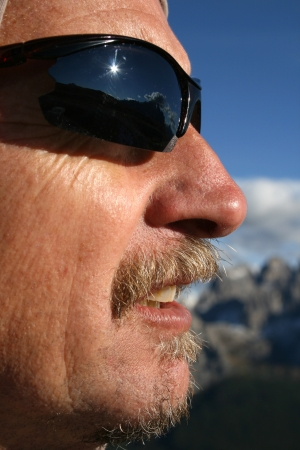 Man in sunglasses standing in sun with mountains in background