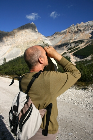 Hiker with binocluars in the hand in Dolomites, Italy Stock Photo