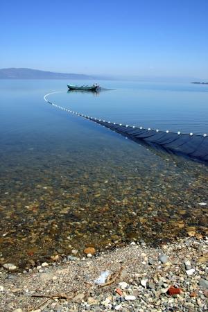 Small fishing boat and wide fishing net on a lake at Iznik, Turkey   Stock Photo