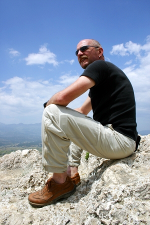 Mature man sitting on some rocks staring out to sea