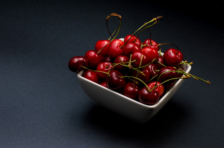 Cherries Bowl on dark background photo