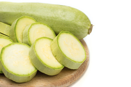 Zucchini on circle wooden plate on white isolated background photo