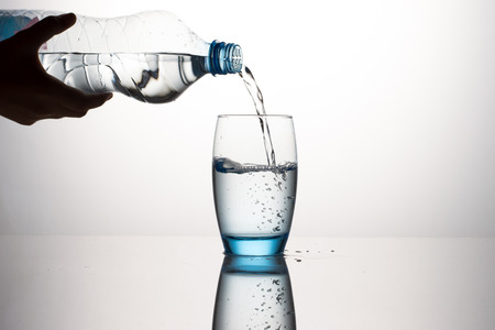 pouring water: Pouring Water in Wateglass on Gray Background Stock Photo