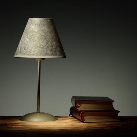 Minimalist lamp on retro background with books education concept photo