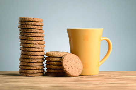 Mug of milk and cookies on vintage wooden background photo