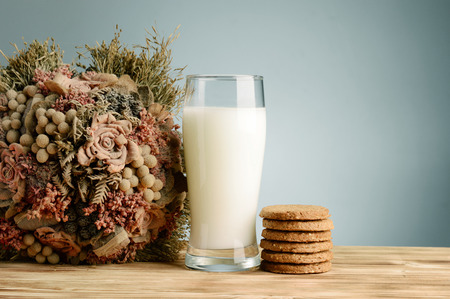 Glass of milk and cookies on vintage wooden background with dried flower bouquet photo