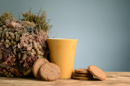 Mug of milk and cookies on vintage wooden background with dried flower bouquet photo