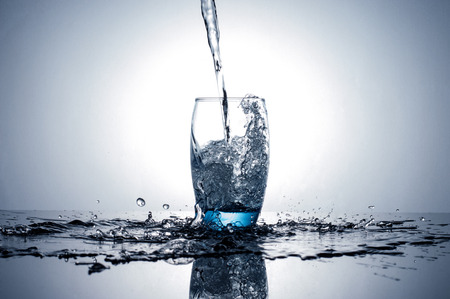 Water flowing and splashing into a glass