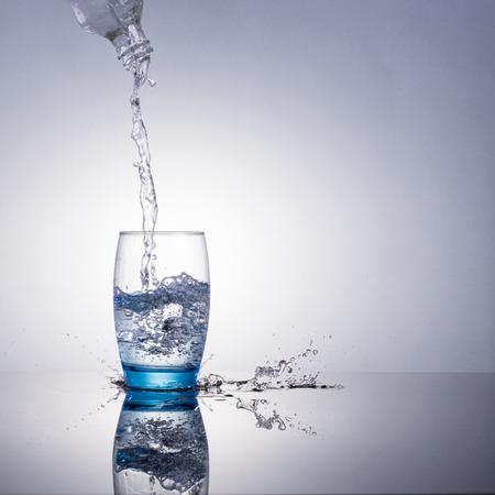 acqua vetro: L'acqua che scorre e spruzzi in un bicchiere Archivio Fotografico