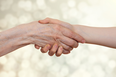 Handshake between an old person with a wrinkled hand and a kid, on a beige bokeh  light background.