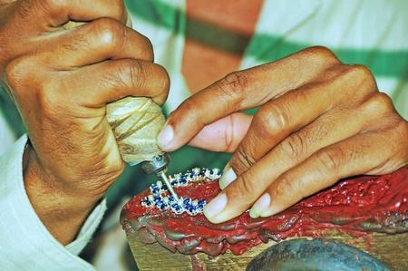 An artisan creates the head of a jewel.