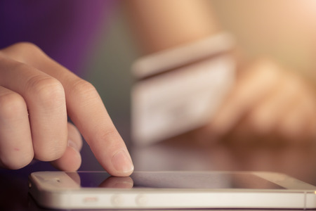 cvv: Online payment,Womens hands holding a credit card and using smart phone for online shopping