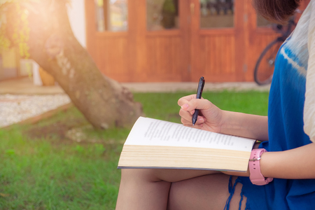 Young woman reading and mark something on book sitting in garden. Vintage filter effect. Stock Photo