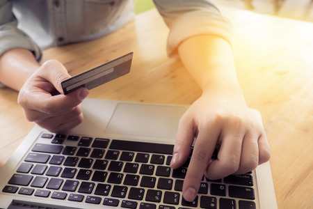 cvv: Mans hands holding a credit card and using pc or laptop for online shopping.