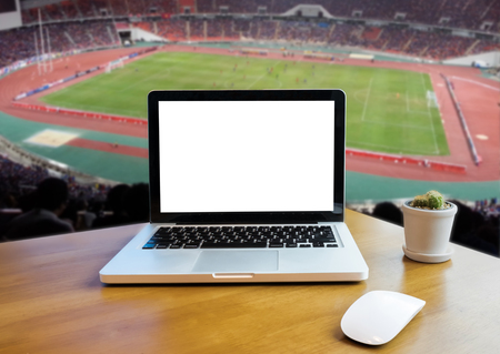 Front view of laptop on desk outdoor office and football stadium blurred background. Laptop with blank screen and can be add your texts or others on Laptop. Laptop concept.soft focus. Stock Photo