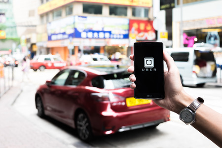 HONGKONG,CHINA - MAY 16,2016 : A man hand holding Uber app showing on LG G4 on road and red car,Uber is smartphone app-based transportation network.