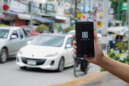 CHIANG MAI,THAILAND - JULY 17, 2016 : A man hand holding Uber app showing on LG G4 on road and red car, Uber is smartphone app-based transportation network.