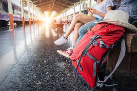 Two backpacker and hat at the train station and looking on the map for plan to travel.  Travel concept. Stock Photo
