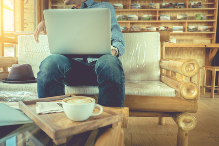 Alone traveler using laptop in coffee shop at morning. Travel and Relax concept.