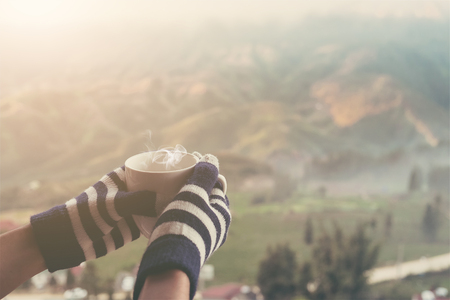 hands holding hot cup of coffee or tea in morning sunlight with beautiful mountain with fog and cloudy background. vintage filter
