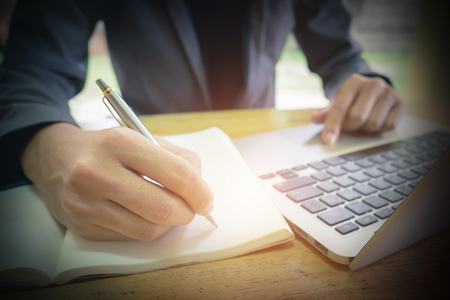 Business man using pen and laptop then writing on notebook at workplace. Stock Photo