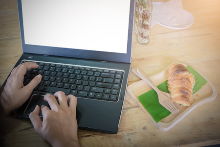 Business woman hands using laptop with blank screen and croissant on banana leaf at morning on wooden desk in home interior. vintage filter effect. Stock Photo