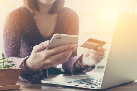 cvv: Online payment, Womans hands holding a credit card and using smart phone for online shopping in coffee shop