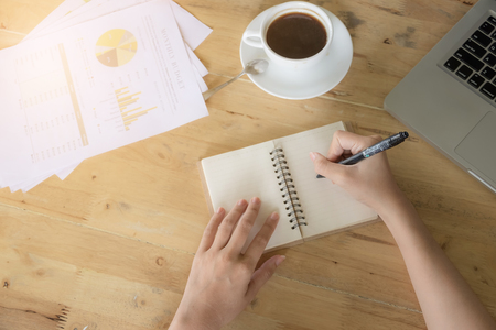 Business women writting on notebook and hot coffee and turnover document papaer sheets on wooden table in home office with morning light.