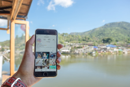 CHIANG MAI, THAILAND - DEC 25, 2016: A man hand holding iphone with new logo of instagram application. Instagram is largest and most popular photograph social networking.