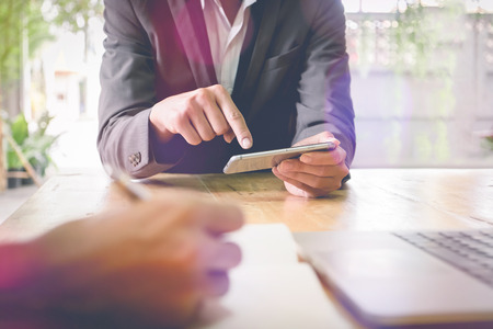 Close-up of two business man hands pointing at smartphone while discussing it on wooden table in office. group concept. Stock Photo