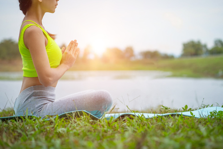 Young woman practicing yoga on the field.