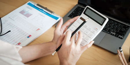 Close up of woman calculating financial or taxes or household on calculator, female calculate while sitting at her home and make payment.