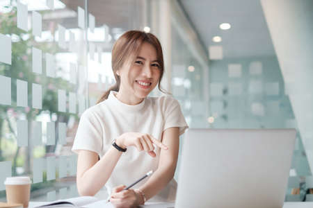 Positive beautiful woman happy with her job and work from home. business, account, finance, tax concept. Stock Photo