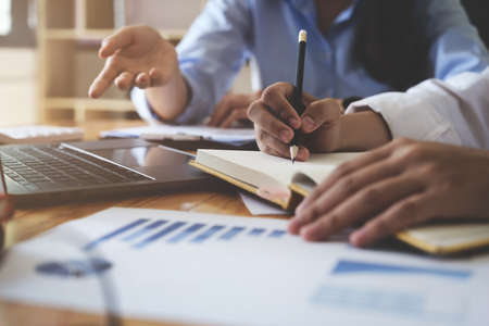 A group of business people are meeting to analyze data for marketing plan with paperwork. Stock Photo