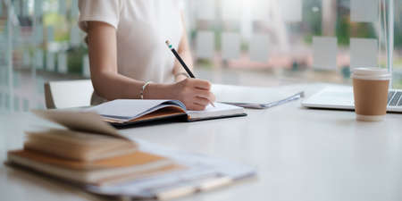 Concept of finance economy, banking business and stock market research. Business accountant or financial holding pencil writing at notebook on desk. Stock Photo