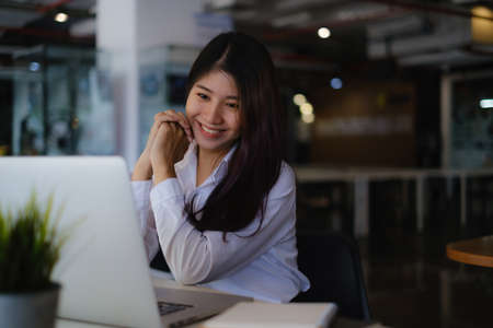Joyful businesswoman sitting at desk looking at laptop screen talking with friend make informal video call.