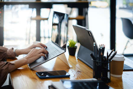 Fashion asian woman designer using digital tablet with blank screen.