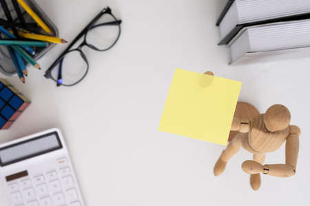 Yellow sticky notes and business tools on white wooden desk. top view.