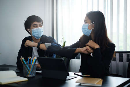 Business or accountant wear mask and bumping elbows for keeping social distance instead of hugs or handshake at morning in home office.