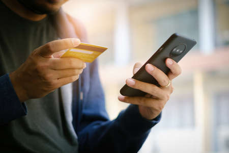 A young man makes a purchase on the Internet on the smartphone with credit card. Shopping online concept..