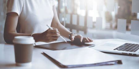 Casual business woman writing on notebook in home office. Business planning, tax, account, financial concept.
