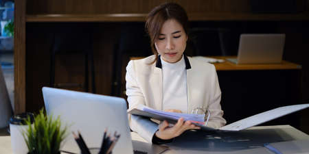Joyful businesswoman sitting at desk looking at paperwork and talking with friend make informal video call. Stock Photo