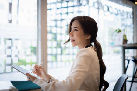 Asian Business woman checking email at morning in office. finance, fund, investment concept. Stock Photo