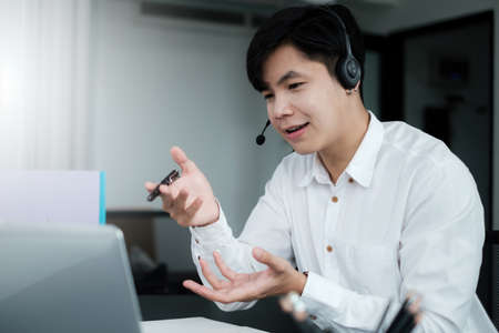 Businessman discuss with partners by video call. Male technical support agent trying to explain something to a client while working on laptop at call center.