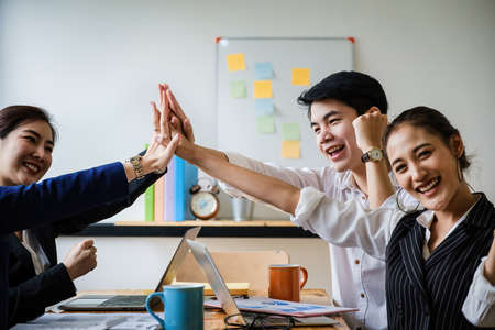 Business team giving a high fives gesture as they laugh and cheer their success. Achievement and Business Goal Success Concept. soft focus.