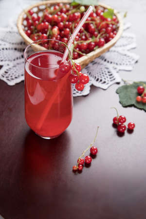 Sprigs of redcurrant berries lie on a wicker plate, and a Morse of berries stands in a glass glass and a tube on a dark table with a knitted napkin. A summer drink that quenches your thirst. Stock Photo
