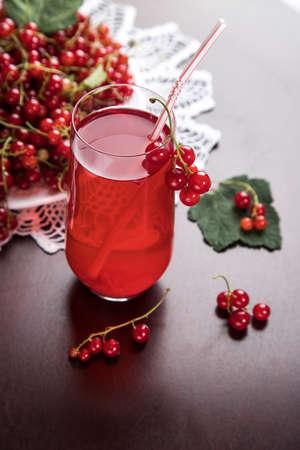 红醋栗浆果枝条在一块白板上,浆果莫尔斯在玻璃杯子里和一块管子在一张黑暗的桌子上与针织的餐巾。夏季饮料淬火你的口渴。